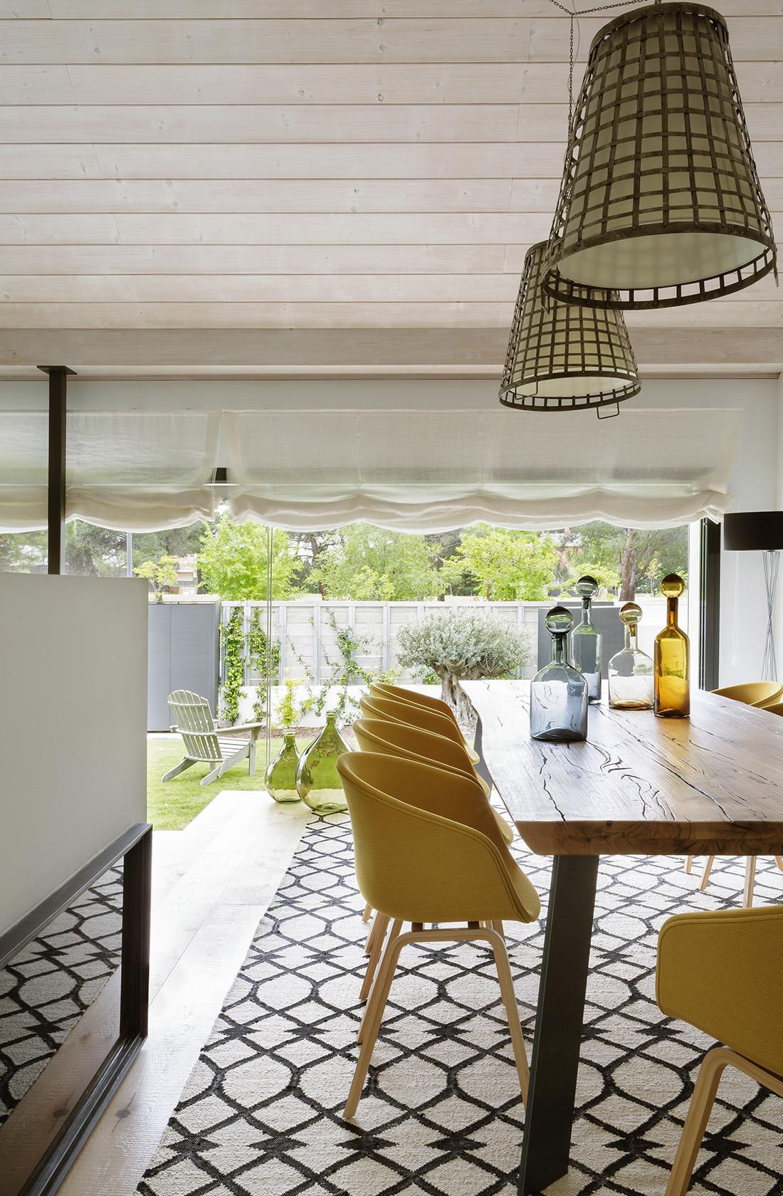 Comedor con vistas al jardín de la Casa XY, un Proyecto de Arquitectura en madera