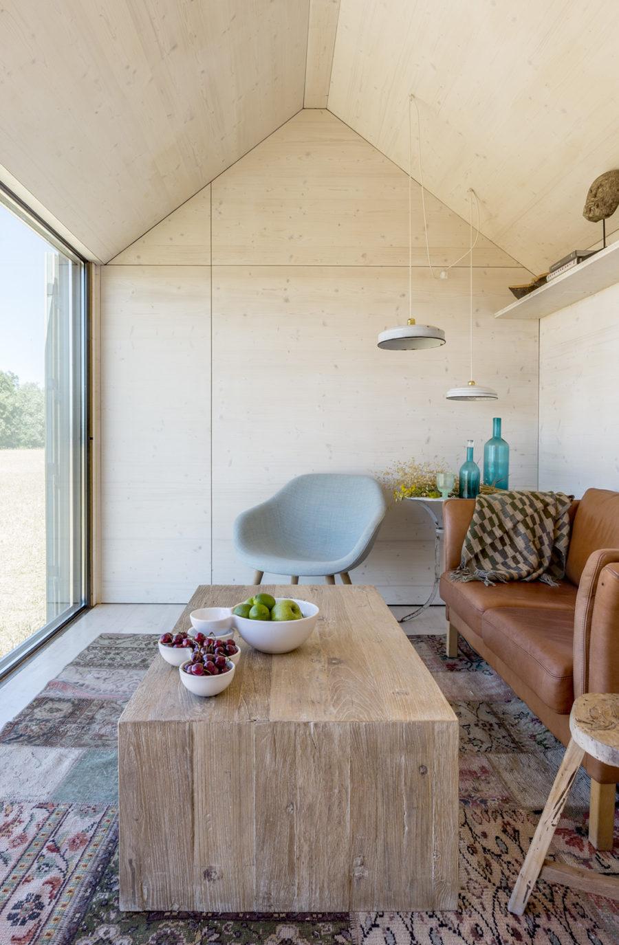 Vista general del salón con paredes y techos de madera de la casa transportable ÁPH