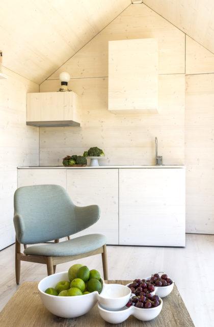 Detalle de la cocina de madera integrada en el salón de la casa transportable ÁPH