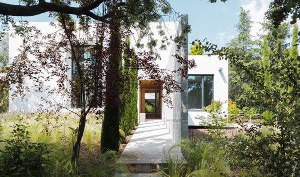 Imagen en miniatura del acceso con vegetación a la Casa CH, vivienda construida en madera