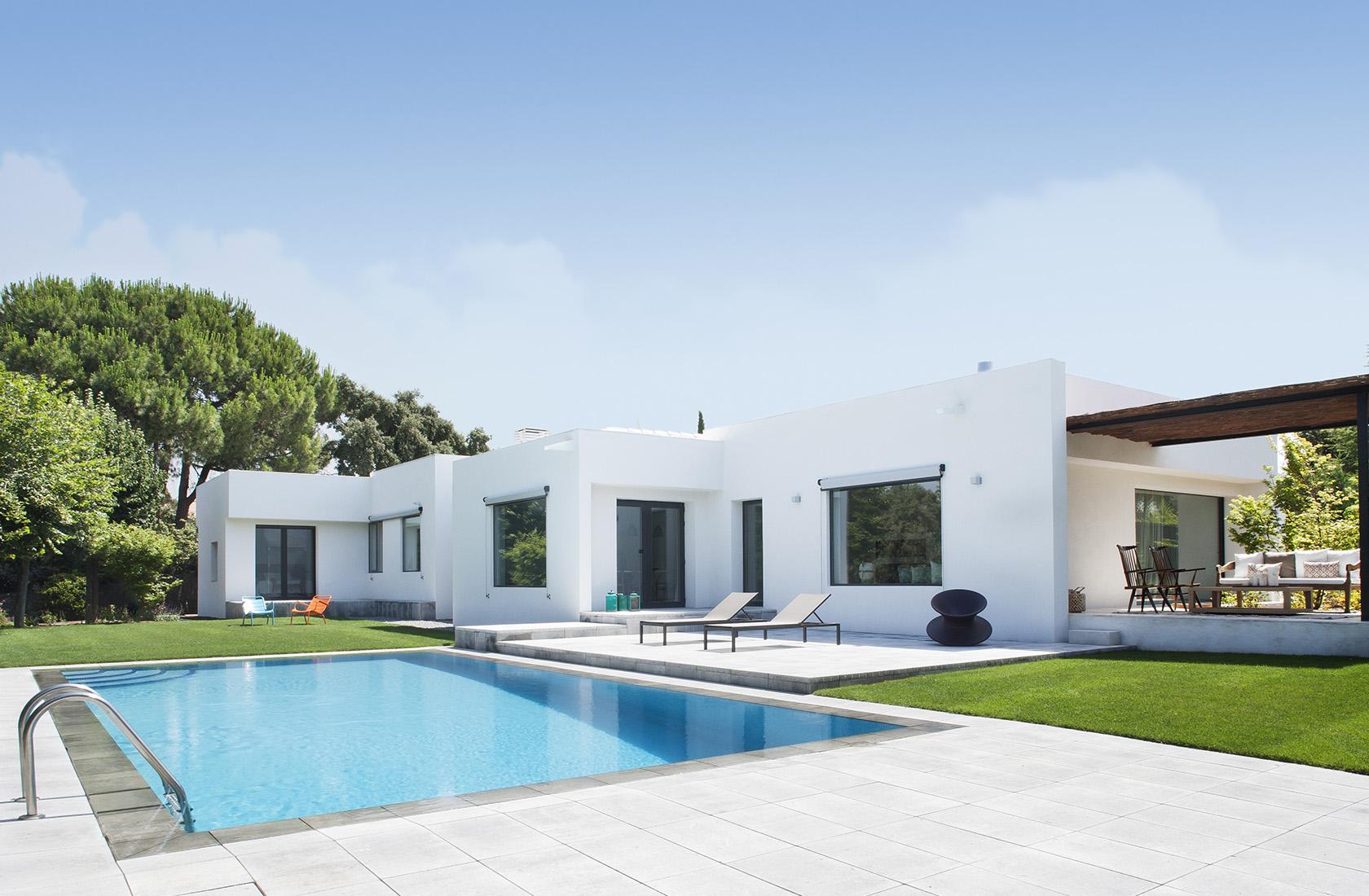 Vista general del piscina y fachada trasera de la reforma integral vivienda en La Moraleja