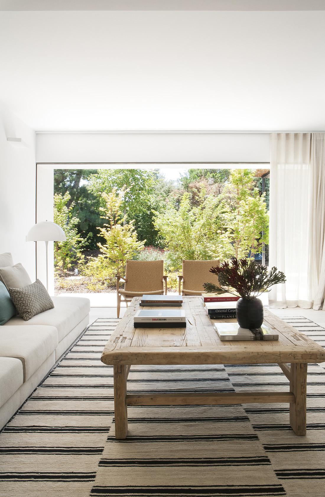 Vista del salón y jardín de la reforma integral en una vivienda en La Moraleja