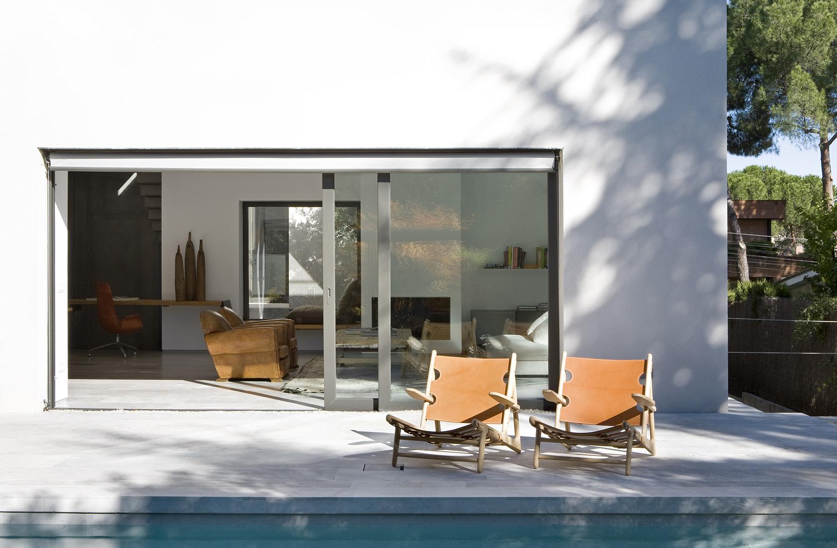 Salón con acceso a la zona de piscina en la sede de ÁBATON Arquitectura